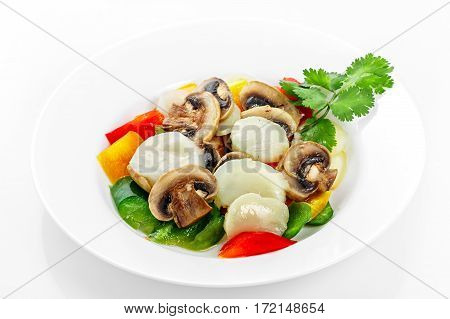 Scallops Salad with mushrooms and vegetables, paprika, scallops on a white plate on a white background