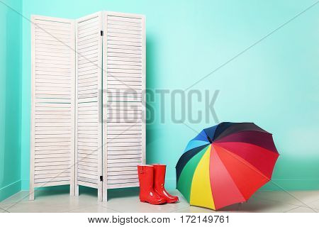 Red Boots With Umbrella Near Wooden Folding Screen On A Green Background