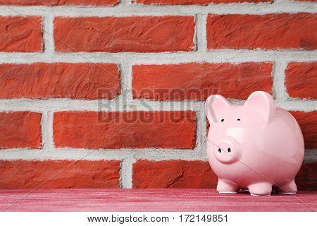 Pink piggy bank on brick wall background