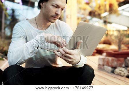 Handsome hipster man working on start-up project on portable laptop computer. Guy in black hat looking ahead in a park sunny day. Business lifestyle concept. Focus on hands.