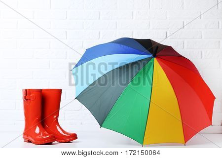 Red Rubber Boots With Umbrella On Brick Wall Background