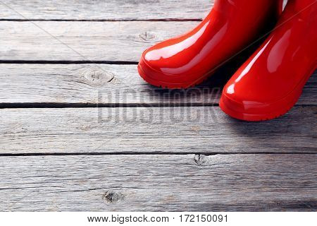 Red Rubber Boots On A Grey Wooden Table