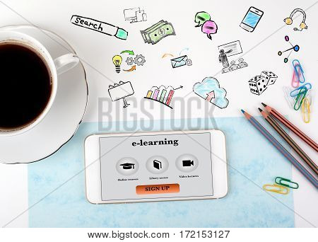 e-learning Concept. Mobile phone and coffee cup on a white office desk.