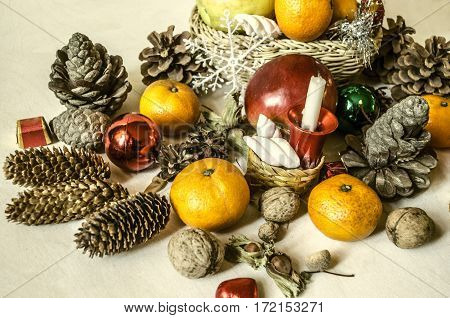 Mandarins,nuts,snowflakes,balls,straw baskets with fruits and sweets on light wooden table