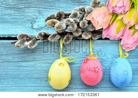 Happy Easter. Pussy-willow and colorful eggs on a blue wooden background.