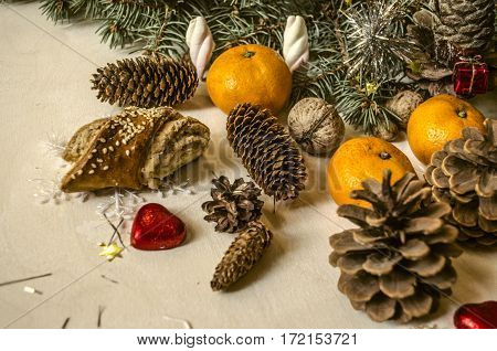Coniferous branch with different pine cones,tangerines, with red hearts on light table