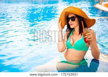 Beautiful Brunette Woman Wearing A Hat And Sunglasses, Enjoying Cocktail In A Swimming Pool, Summer