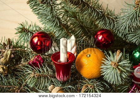 Pine branch with a candle, tangerine and Christmas toys