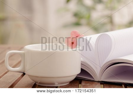 Couple of Crown-of-thorns flower and a cup of tea on wooden table with heart shape which made by white paper notebook. Bright nature background.Vintage color.