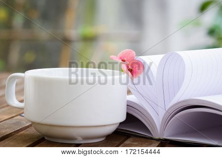 Couple of Crown-of-thorns flower and a cup of tea on wooden table with heart shape which made by white paper notebook. Bright nature background.