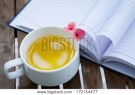 Couple of Crown-of-thorns flower and a cup of tea on wooden table with heart shape which made by white paper notebook