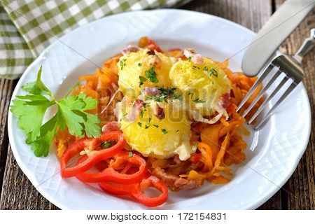 Hearty potato dumpling  gratin with cheese and bacon served on paprika cabbage