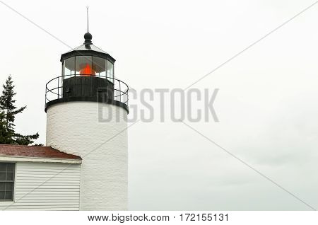 A close up of the Bass Harbor lighthouse with a red light