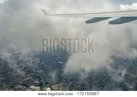 Sydney, Australia - Oct 29, 2016: Plane ascending out of Sydney Kingsford-Smith International Airport, at cloud level. Below is Sydney suburbia.