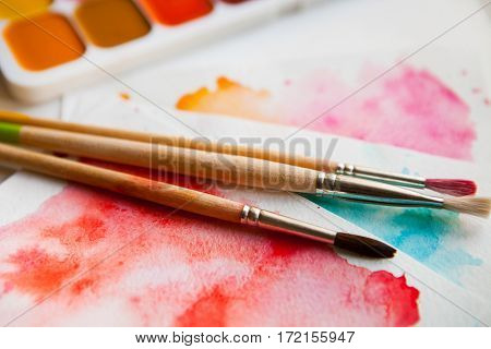 Palette Of Watercolor Paints, Brushes And Paper For A Water Color On White Background, Close Up.