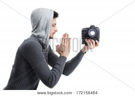 young professional photographer in shirt prays for DSLR digital camera isolated on white background