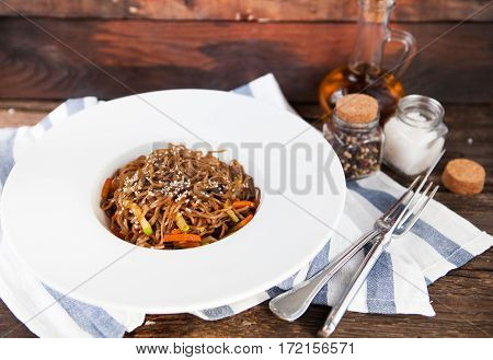 Tasty Soba Noodles With Vegetables In Sweet And Sour Sauce On Old Wooden Background, Close Up