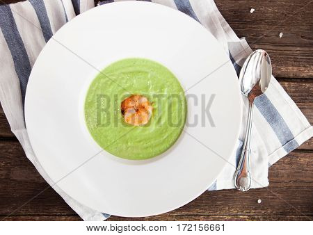 Green Cream Of Asparagus Soup With Shrimp In A White Bowl On A Rustic Background