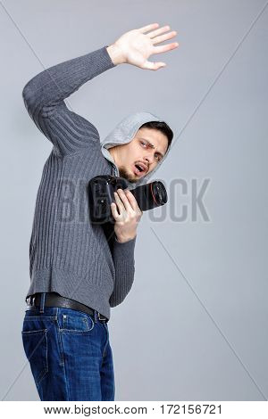 young scared photographer in shirt with DSLR digital camera photographer closes by hand on grey background