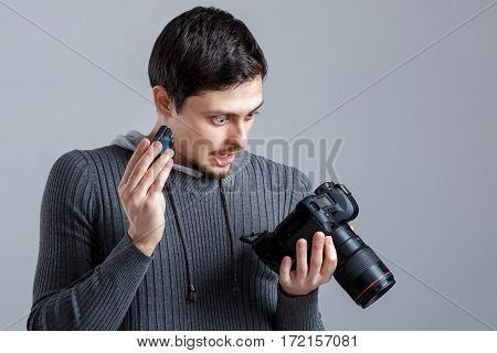 young surprised photographer in shirt is trying to insert the battery in DSLR digital camera on grey background