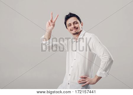 portrait of handsome young smiling Brunet man in white shirt showing thumbs up gesture on gray background. soft light
