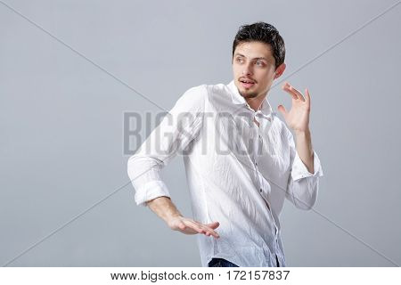 handsome young brunette man in a white shirt dancing and having fun on grey background.