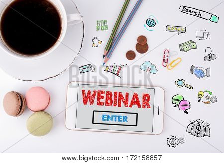 Webinar concept. Mobile phone and coffee cup on a white office desk.