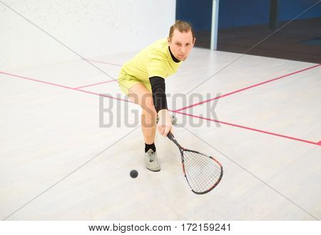 young caucasian squash player hitting a ball in a squash court. Squash player in action. Man playing match of squash