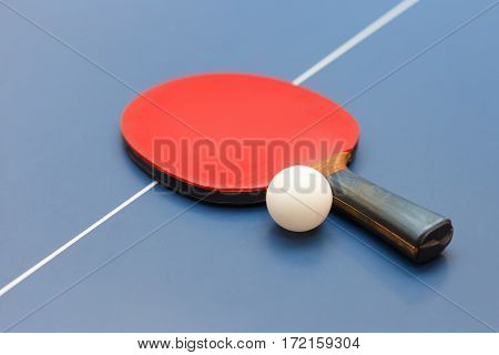 Table tennis red racket and white ball on blue board. Equipment for table tennis. Ping pong. Indoor games