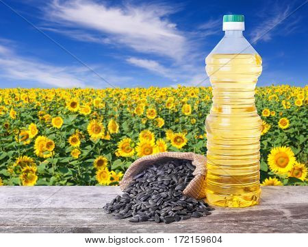 Sunflower oil in plastic bottle and seeds on wooden table with blossom field on the background. Sunflower field with blue sky. Photo with copy space area for a text. Agriculture and harvest concept