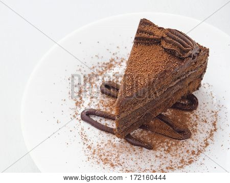 Piece of chocolate cake isolated on white plate. Slice of fresh brownie arranged on white plate.  Copy space for your text. Selective focus on the front.