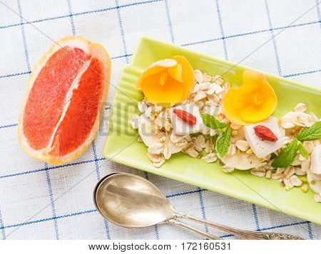 Ingredients for diet vegan breakfast - grapefruit, banana, tofu cheese and oats goji berries on green plate checkered napkin. Copy space top view