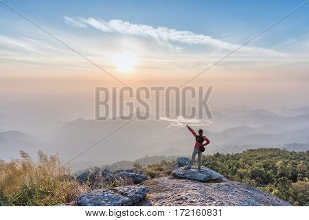 Woman successful climbing standing on the cliff and pointing to the sun.