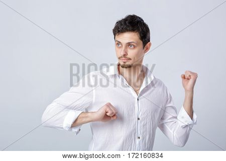 portrait of young attractive man with dark hair in a white shirt ready for fight on grey background.
