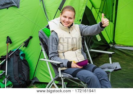 Positive young woman showing thumbs up, enjoy a tasty food during the camping holidays. In the background tourist tent and equipment for outdoor activities.