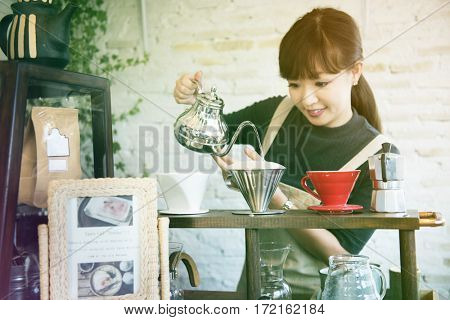 Young woman barista making coffee in cafe