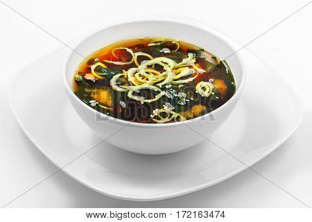 Miso soup, seaweed, tofu, mushrooms, leek, white background