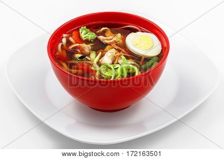 Chicken noodle soup, paprika, zucchini, carrots, wheat udon noodles, chicken, leek, white background