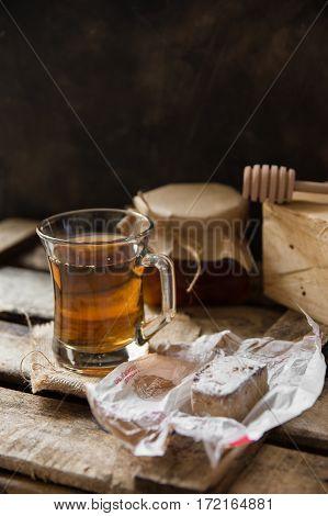 Cup of hot herbal tea jar with honey dipper Spanish christmas cookie polvoron on vintage wood box homeley cozy atmosphere selective focus