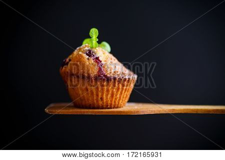 sweet muffins with berries inside on a wooden table