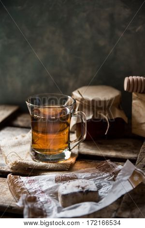 Glass cup with hot tea with jar of honey or jam wood spoon Spanish cookie polvoron on vintage box grey wall backgroundrustic vintage interiorcozy atmosphere