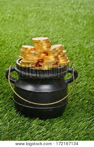 closeup black pot of gold on grass