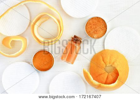 Citrus extract cosmetics, orange essential oil, fruit peel, facial scrub in jars, top view wooden table.