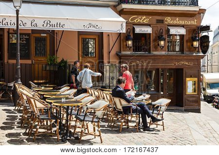 Paris France - June 28 2016: A traditional restaurant in Paris in the Butte Montmartre. Middle aged man sitting in a french terrace with smartphone and coffee under the sun.