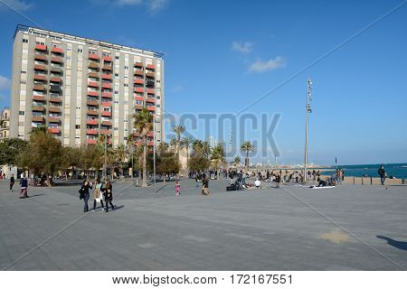 Barcelona Spain - December 3 2016: Building and unidentified people on square at sea shore in Barcelona Spain
