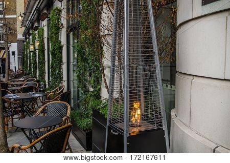 front of the restaurant tables outside for customers prepared gas lamp for heating green plants on the wall