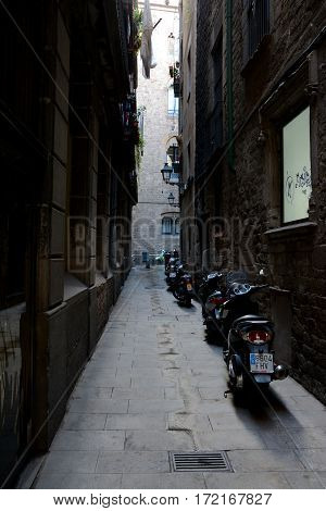 Barcelona Spain - December 3 2016: Scooters standing on narrow dark street in Barcelona city Spain.