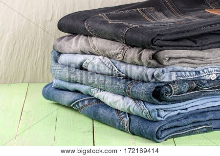 a stack of jeans on a green wooden background.