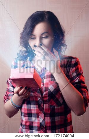 Sexy model girl in plaid shirt opens a Valentine gift. Happy woman, women's day. The brunette lady surprised by bright magic light out of the box.