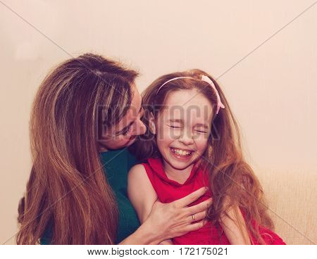 Motherhood is pure joy. Beautiful young woman hugging little girl smiling and looking at her with love. Mother and daughter having fun together